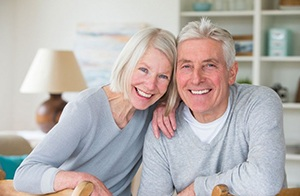elderly couple in gray sweater smiling