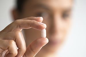 Hand holding an antibiotic pill