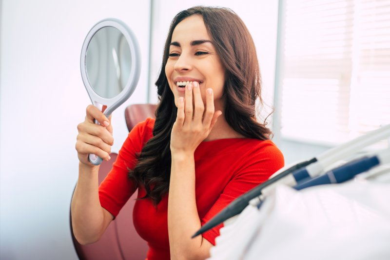 Woman looking at her dental implant in the mirror